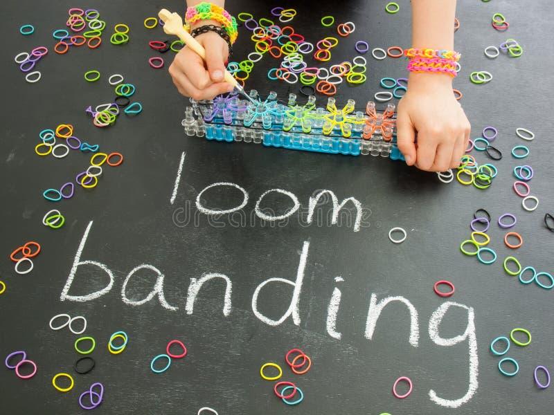 Main de Childs utilisant un métier à tisser de bande sur un tableau noir avec images libres de droits