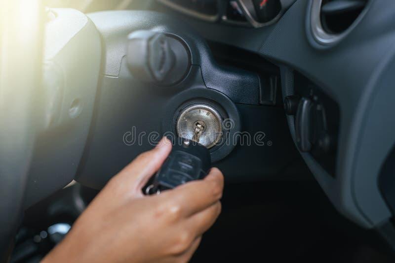 Main de clé d'insertion de l'homme au système de voiture de début, bouton sur le tableau de bord dans la voiture photo libre de droits