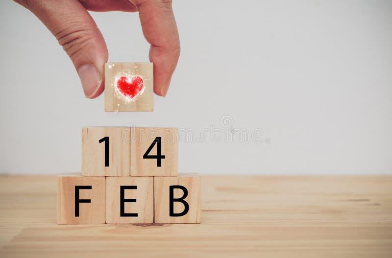 Main de conceptman du jour de valentine d'amour tenant le coeur pour mettre dessus le cube en bois pour signifier l'amour le jour image stock