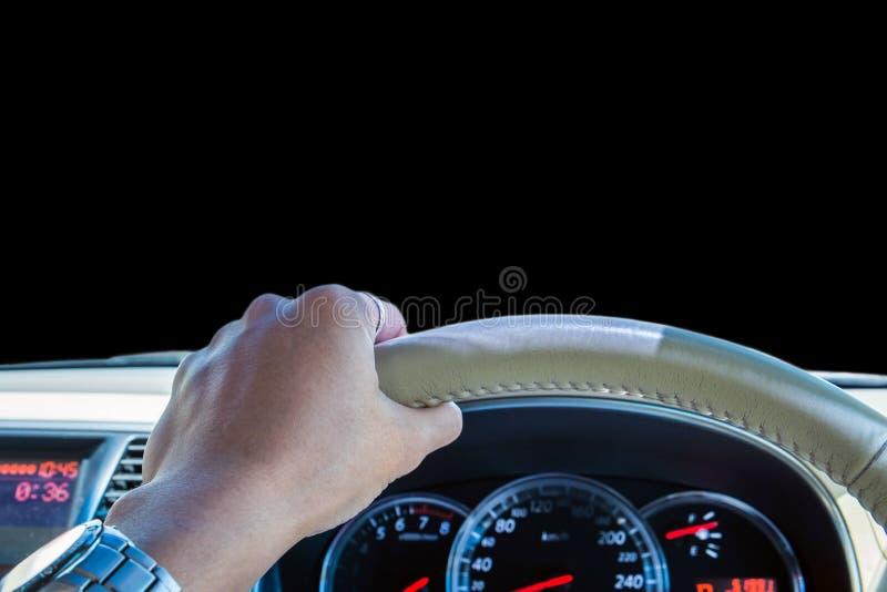 Main de conducteur tenant le volant avec la console d'avant de voiture, vue de face d'isolement sur le fond noir photo stock