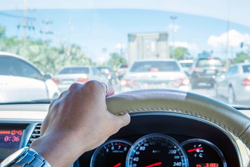 Main de conducteur tenant le volant, avec la vue du trafic dans la ville photographie stock