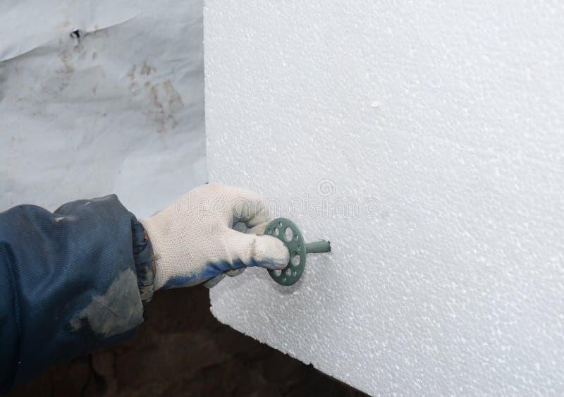 Main de constructeur installant le panneau isolant rigide de mousse de styrol avec le clou en plastique, support image stock