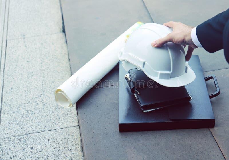 Main de construction haute étroite tenant le chapeau sur le ciment photographie stock