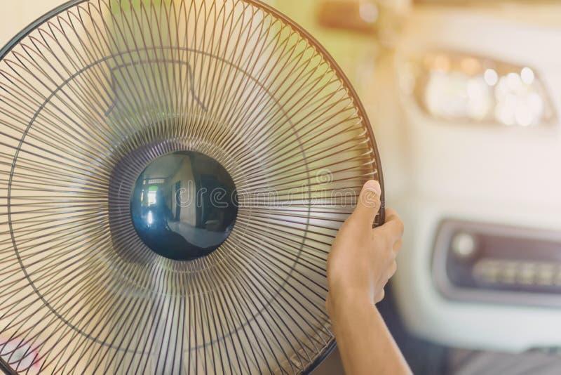 Main de contact de jeune homme et s'ajuster sur les grils avant du ventilateur électrique à un bon vent dans sa maison en été photo libre de droits