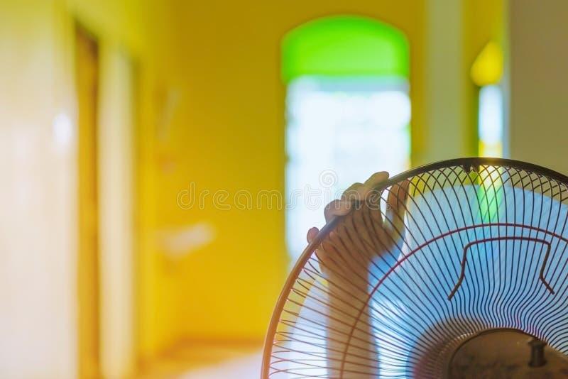 Main de contact de jeune homme et s'ajuster sur les grils avant du ventilateur ?lectrique ? un bon vent dans sa maison en ?t? photos libres de droits