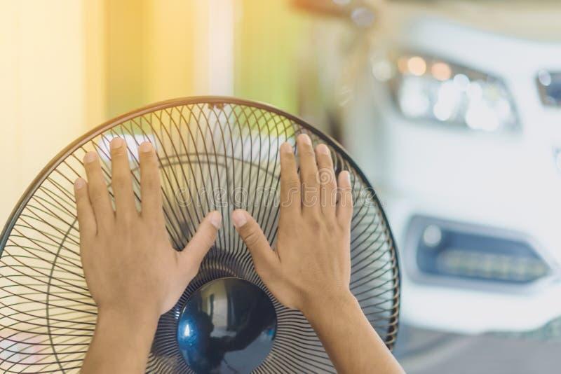 Main de contact de jeune homme et s'ajuster sur les grils avant du ventilateur ?lectrique ? un bon vent dans sa maison en ?t? d'a photographie stock