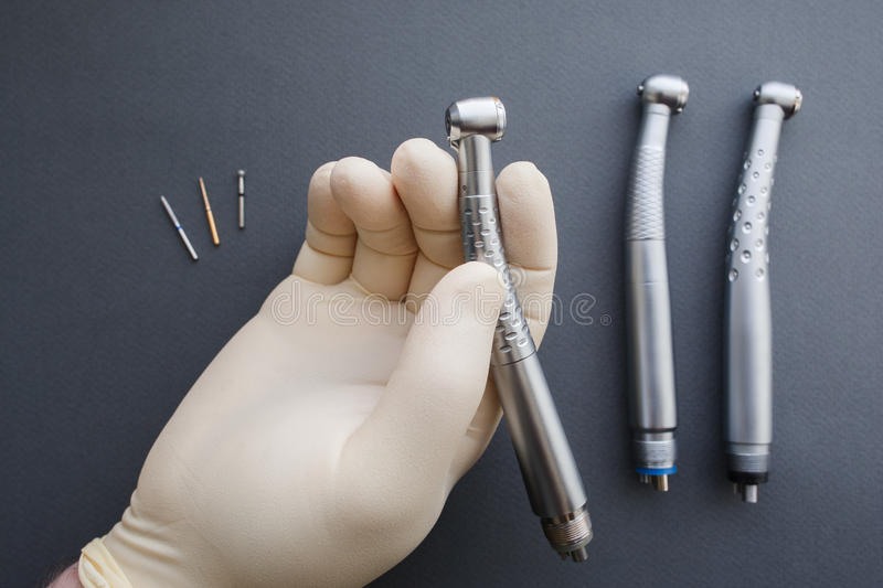 Main de dentiste jugeant le handpiece dentaire en gros plan photos stock
