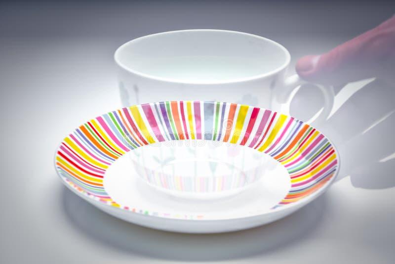 Main de disparaition trouant un service à thé coloré et élégant de tasse et soucoupe de café - d'après-midi photo stock