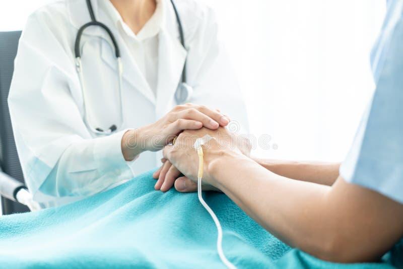 Main de docteur féminin rassurant sur son patient supérieur photographie stock