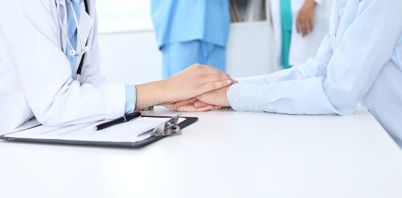 Main de docteur rassurant son patient féminin Éthique médicale et concept de confiance, fond blanc images stock