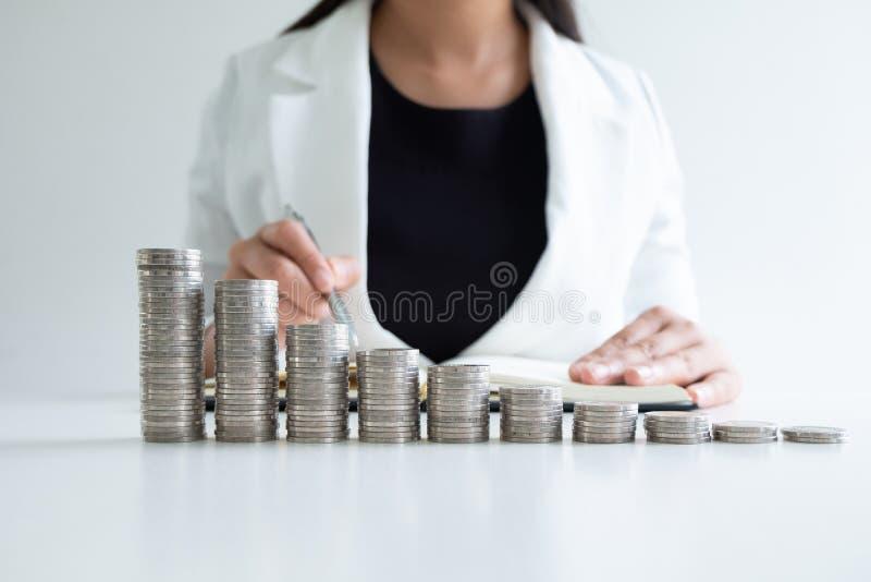 Main de femme écrivant des pièces de monnaie de sa barre analogique de pièces de monnaie photos libres de droits