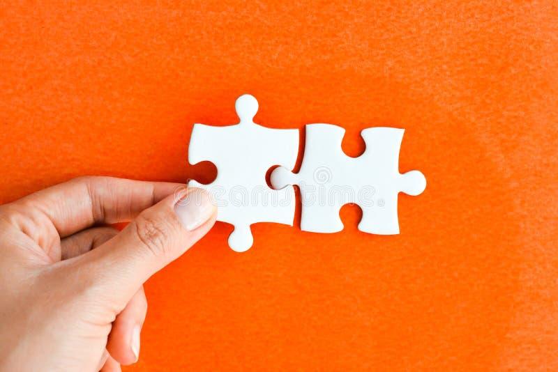 Main de femme adaptant le bon morceau de puzzle suggérant le concept de mise en réseau d'affaires photographie stock libre de droits