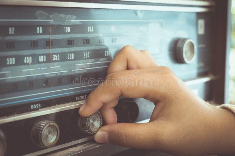 Main de femme ajustant le récepteur radioélectrique de vintage de bouton photo libre de droits