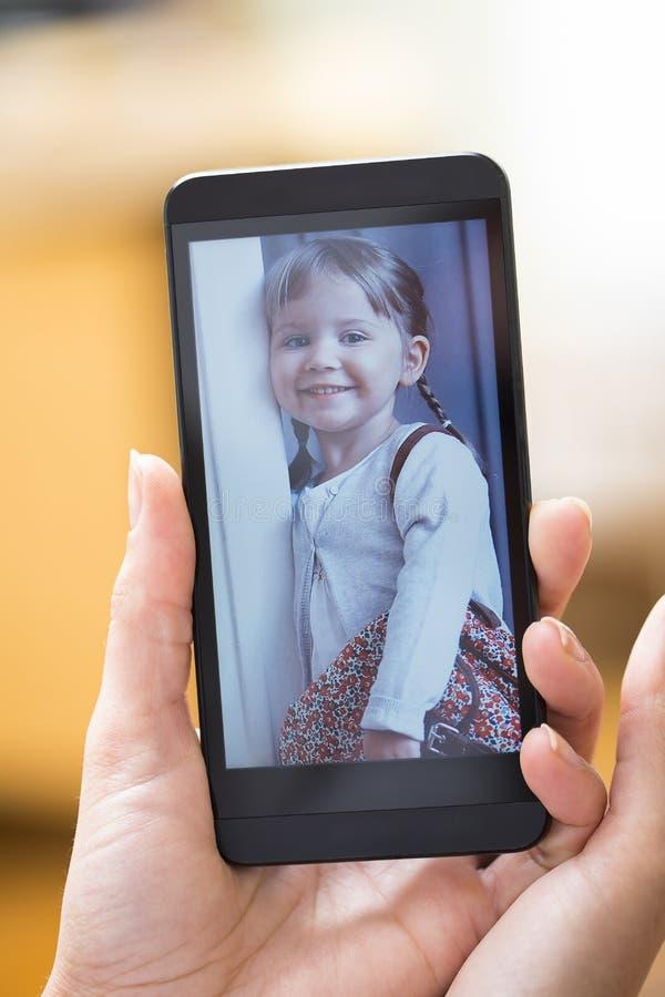 Main de femme avec la photo d'enfant d'apparence de smartphone photos libres de droits