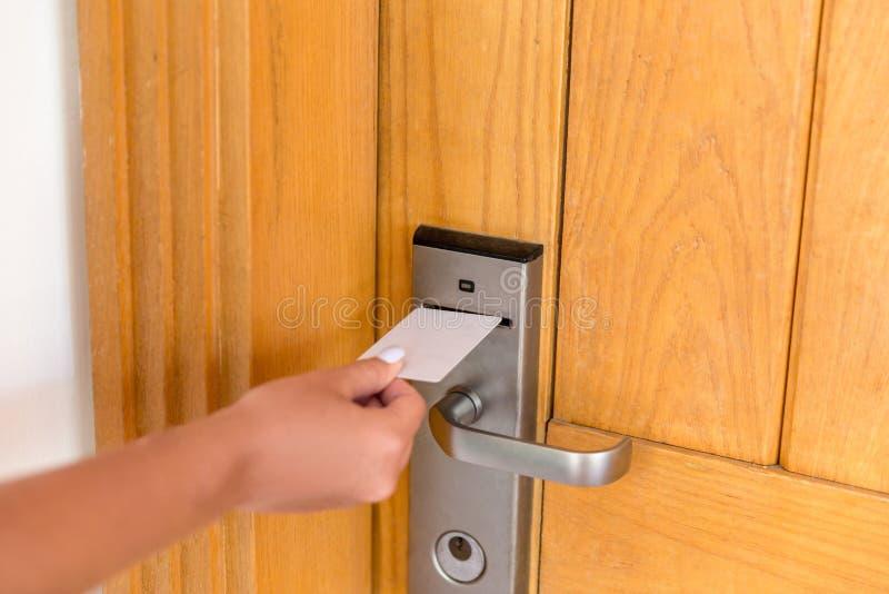 Main de femme avec le keycard dans la serrure électronique carte principale de prise femelle de main et porte de serrure électr images libres de droits
