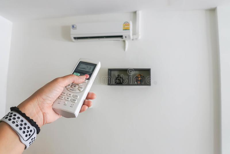 Main de femme avec le panneau à télécommande de climatiseur pour l'arrangement de température images stock