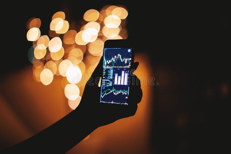 Main de femme avec le téléphone portable avec l'affichage d'opérations boursières dans l'obscurité avec le fond clair de bokeh photo stock