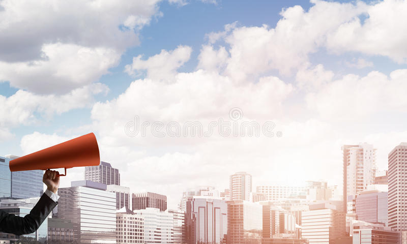 Main de femme d'affaires tenant la trompette de papier rouge sur le fond de paysage urbain photos stock