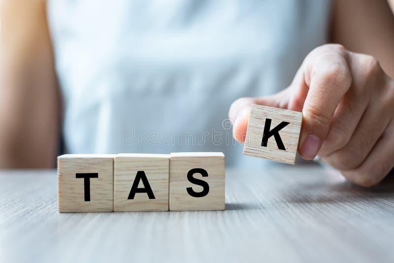Main de femme d'affaires tenant le bloc en bois de cube avec le mot d'affaires de TÂCHE sur le fond de table Concept de liste et  images stock