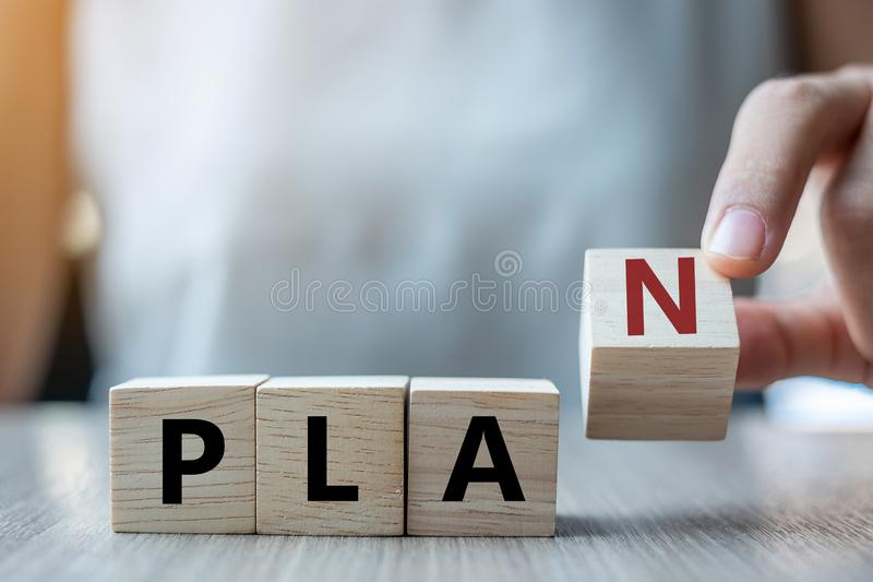 Main de femme d'affaires tenant le cube en bois avec le texte de PLAN sur le fond de table Buts, succès, stratégie, solution et a image libre de droits