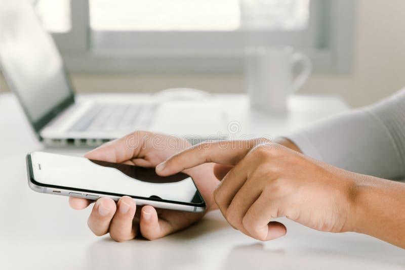 Main de femme de plan rapproché utilisant le téléphone sur l'espace de travail dans le bureau photos libres de droits