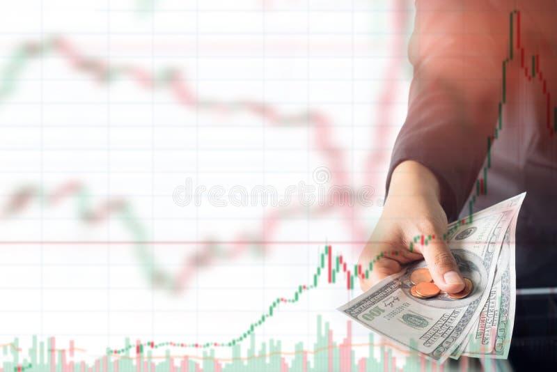 Main de femme donnant l'argent liquide du dollar sur le fond de graphique d'opérations boursières images stock