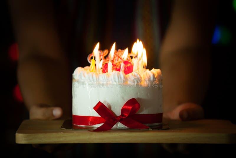Main de femme donnant le gâteau d'anniversaire délicieux avec les bougies brûlantes photo libre de droits