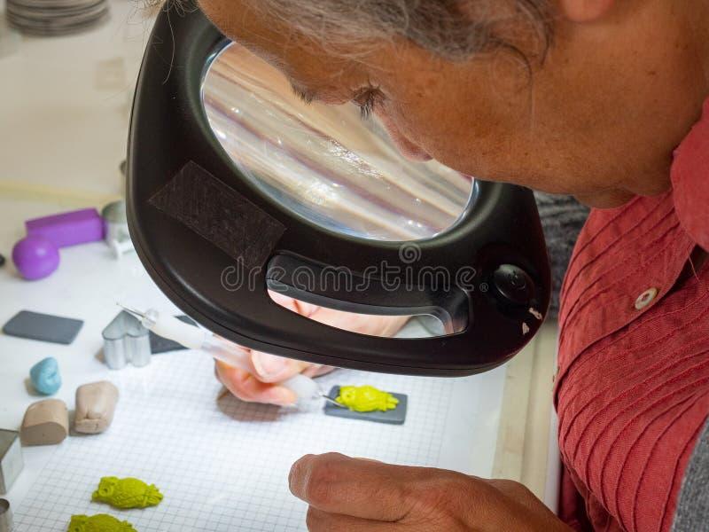 Main de femme faisant le bouton de hibou à partir de l'argile de polymère Passe-temps, fond de travail manuel photos libres de droits