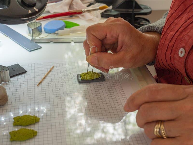 Main de femme faisant le bouton de hibou à partir de l'argile de polymère Passe-temps, fond de travail manuel images stock