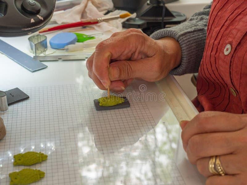 Main de femme faisant le bouton de hibou à partir de l'argile de polymère Passe-temps, fond de travail manuel image stock
