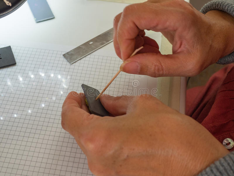 Main de femme faisant le bouton de hibou à partir de l'argile de polymère Passe-temps, fond de travail manuel photo libre de droits
