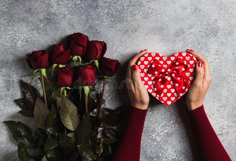Main de femme de jour de valentines tenant le jour de mères de forme de coeur de boîte-cadeau photo stock