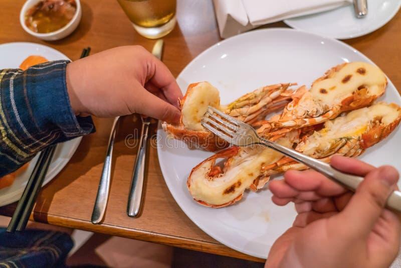 Main de femme mangeant le homard grillé image libre de droits