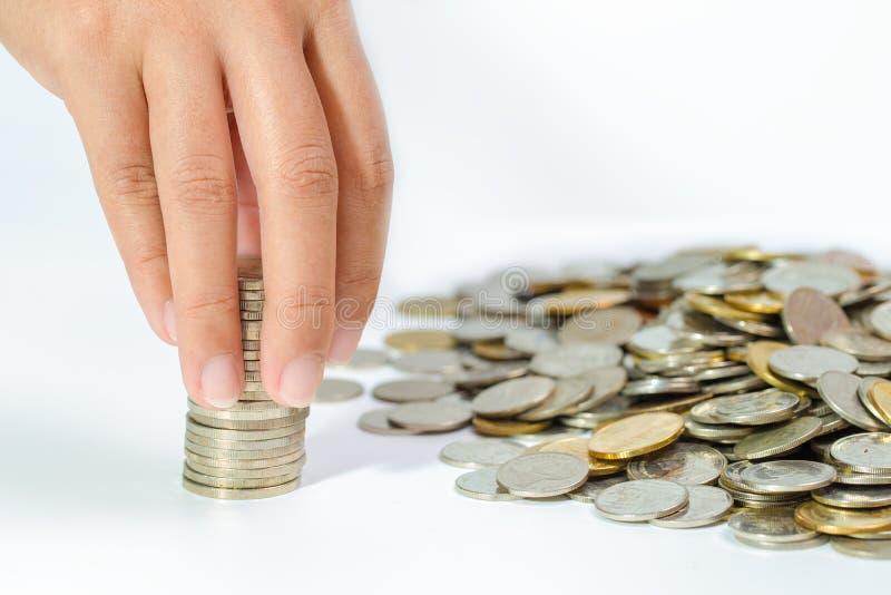 Main de femme mettant la pièce de monnaie à la pile en hausse de pièces de monnaie, enregistrant le mone image stock