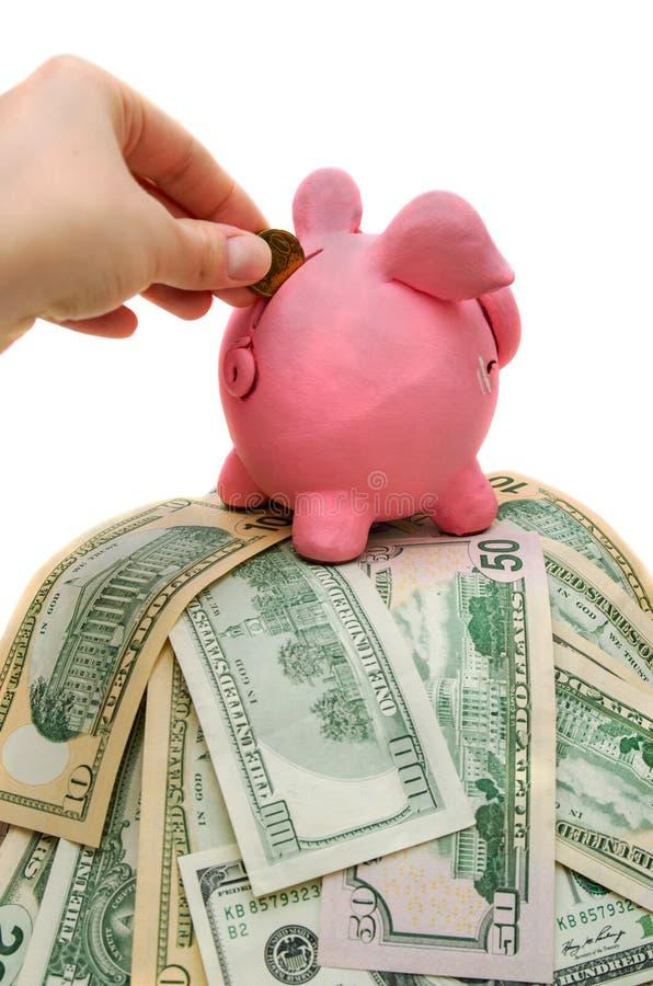 Main de femme mettant la pièce de monnaie à la tirelire avec l'argent image libre de droits