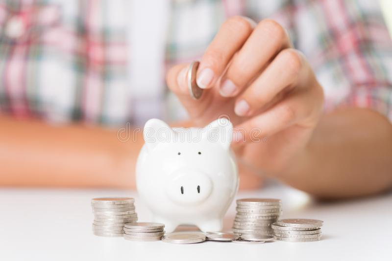 Main de femme mettant la pièce de monnaie d'argent la tirelire et l'en pile de pièces de monnaie image stock