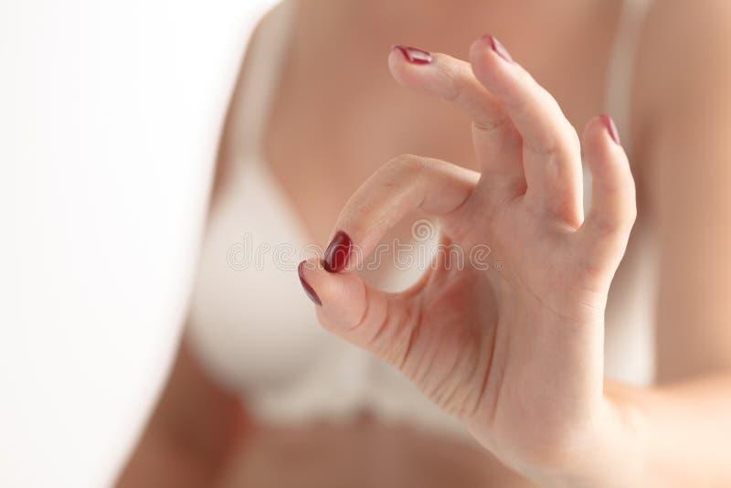 Main de femme de plan rapproché avec la manucure faisant le signe CORRECT photo stock