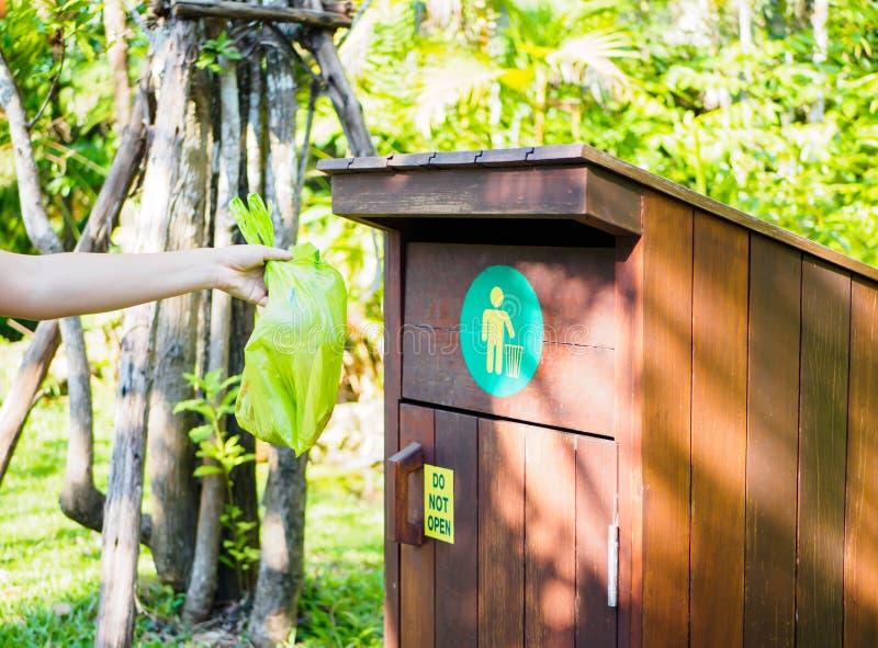 Main de femme de plan rapproché jetant les déchets en plastique dans les déchets photo libre de droits