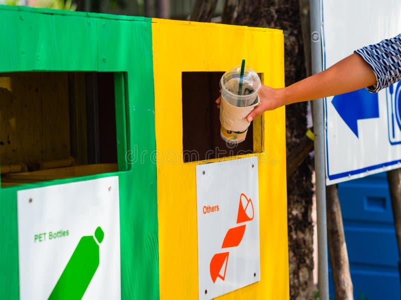 Main de femme de portrait de plan rapproché jetant la tasse en plastique de café vide dans le bac de recyclage photos libres de droits