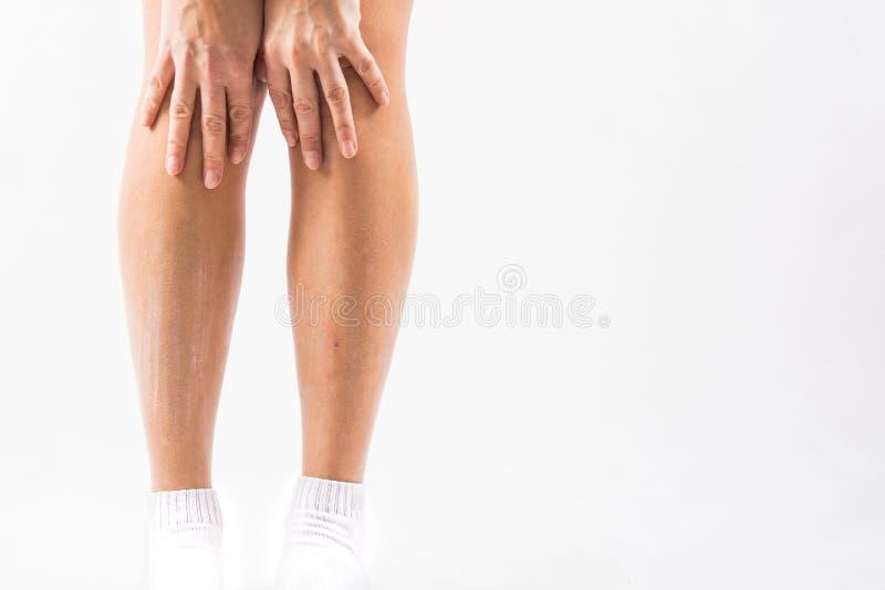 Main de femme rayant sur des pieds avec le fond blanc images stock