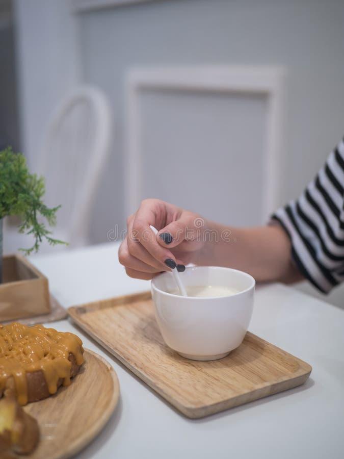 Main de femme stiring le lait chaud photos libres de droits