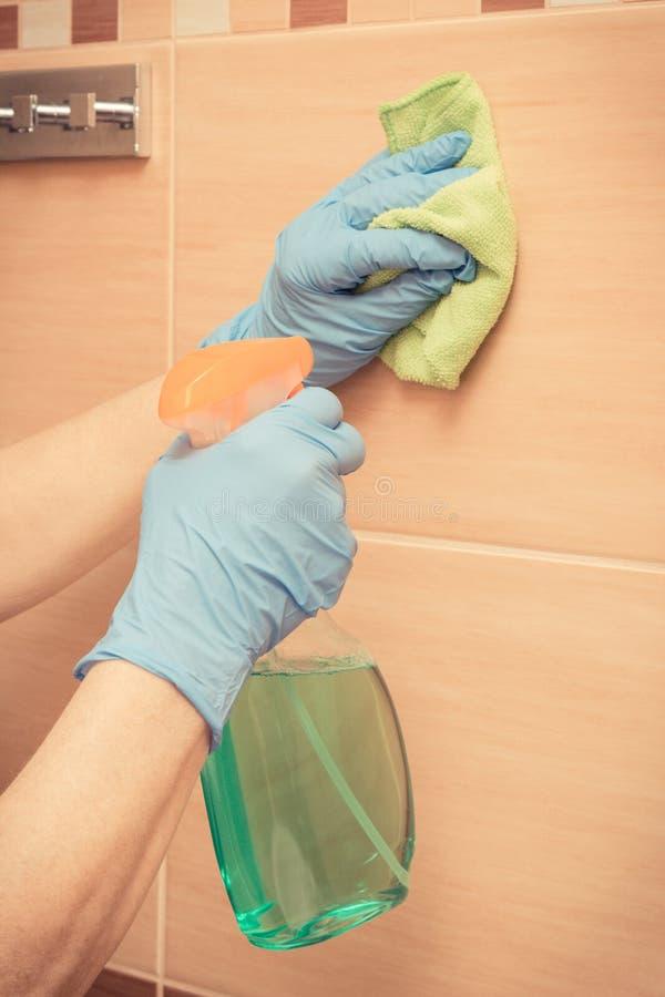 Main de femme supérieure essuyant des tuiles de salle de bains utilisant le tissu de microfiber avec le détergent, concept de fon photo libre de droits