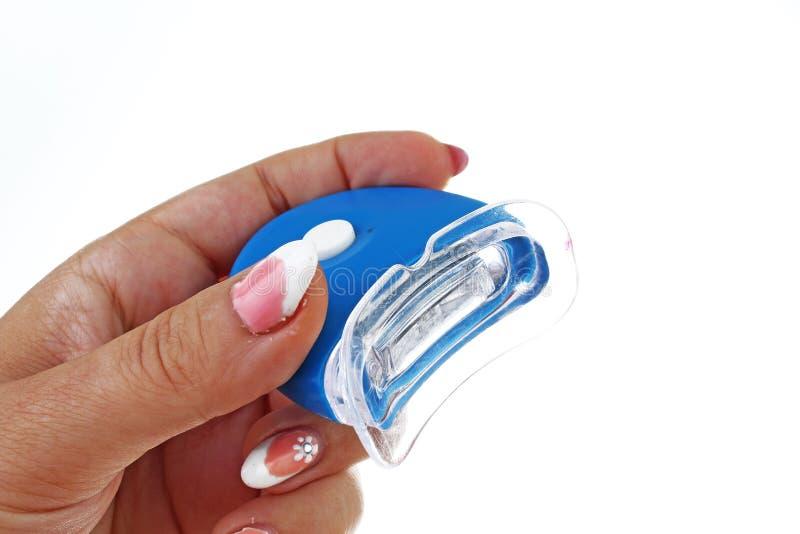Main de femme tenant des dents blanchissant la lumière menée sur le fond blanc d'isolement de coupe-circuit Photo de studio avec  photos libres de droits