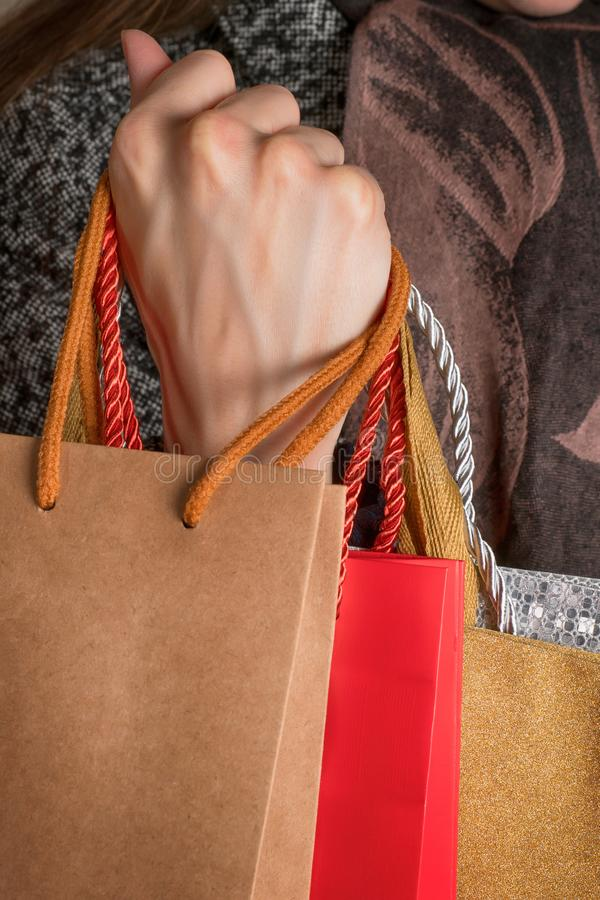 Main de femme tenant de divers sacs de cadeau image libre de droits