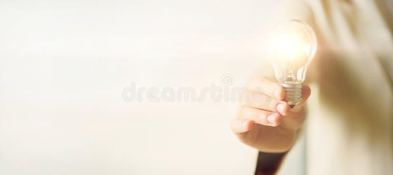 Main de femme tenant l'ampoule sur le fond crème avec l'espace de copie Idée créative, nouveau plan d'action, motivation images libres de droits