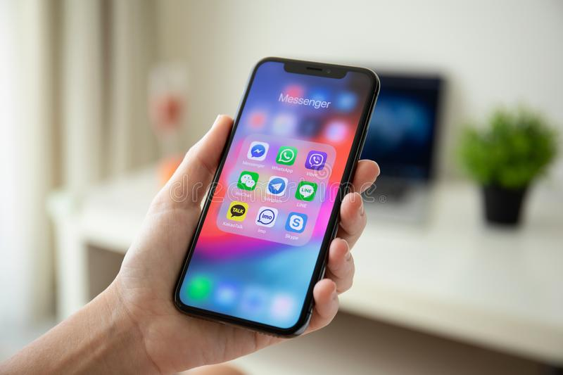 Main de femme tenant l'iPhone X avec le messager social de mise en réseau images stock