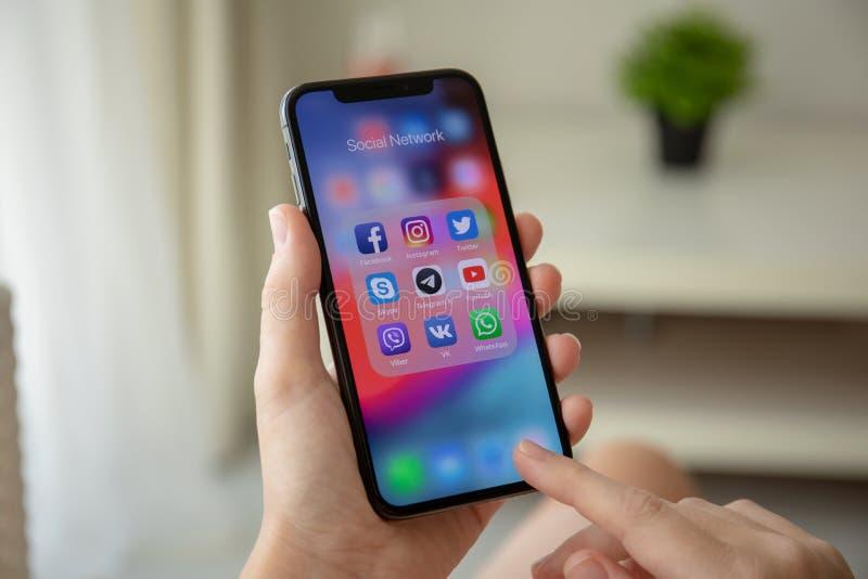 Main de femme tenant l'iPhone X avec le messager social de mise en réseau photo stock