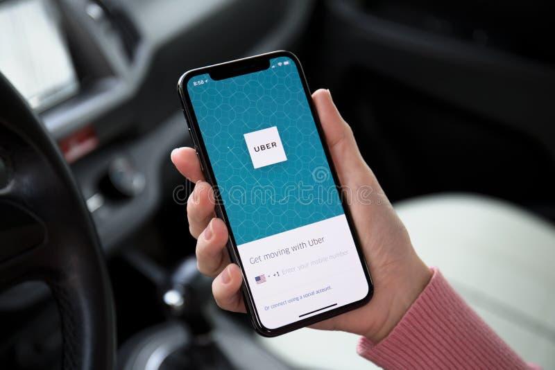 Main de femme tenant l'iPhone X avec le taxi Uber d'application image stock