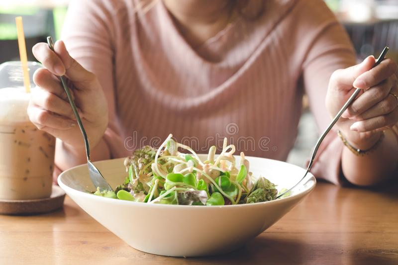 Main de femme tenant la fourchette et la cuillère sur manger de la salade végétale avec photo libre de droits