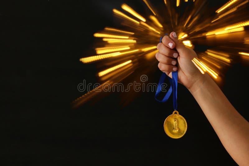 Main de femme tenant la médaille d'or sur le fond noir avec le recouvrement de scintillement concept de récompense et de victoire photo stock